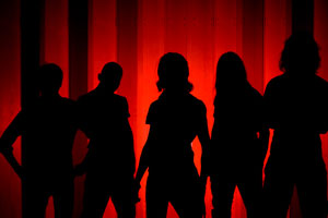 Metalband silhouetted in front of red wall